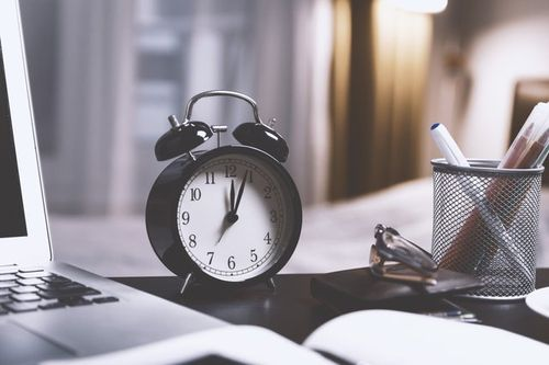 Clock on a freelancer's desk reflecting better time management skills