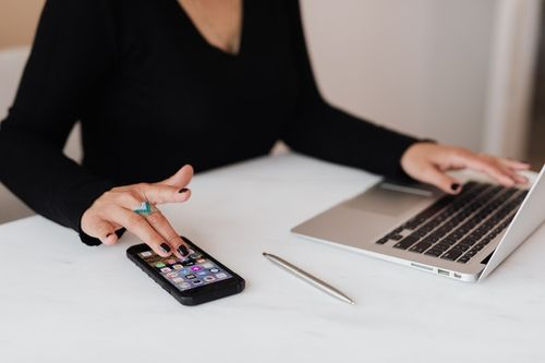 Woman managing lead generation on her computer and cell phone