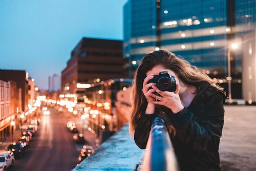 woman taking a photo with canon camera for her photography proposal
