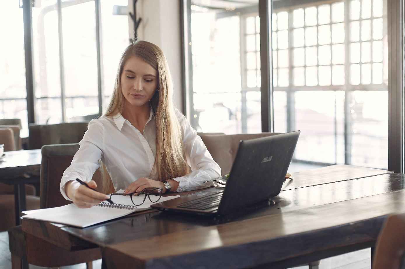 Young focused businesswoman working remotely with copybook in cafe during daytime