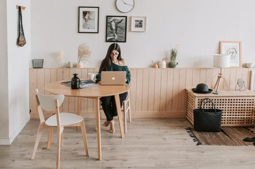 Freelancer sitting in front of her computer in a small office thinking about how many clients she should take on in the year