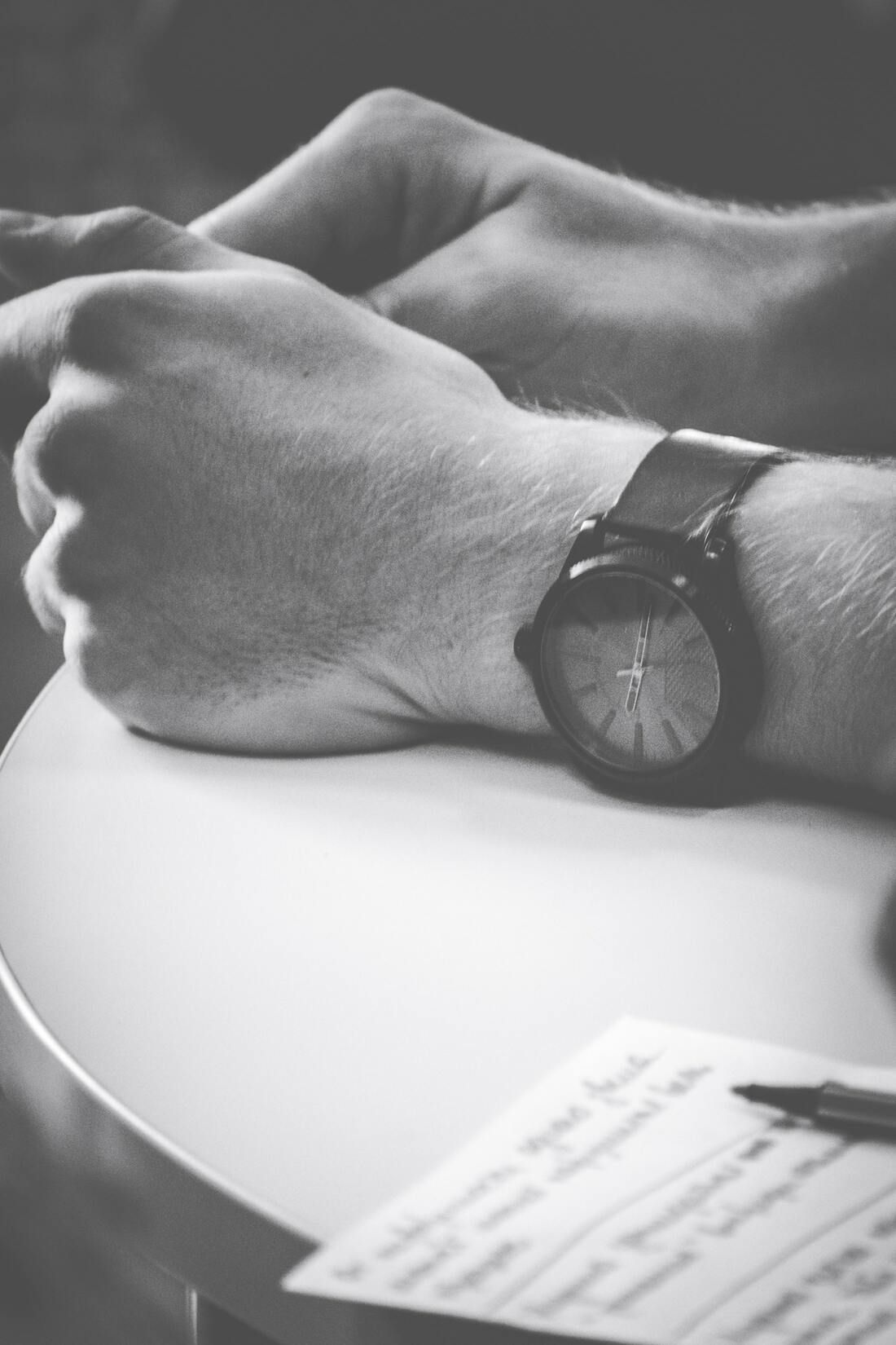 A person tracks time on their freelance project using their wristwatch