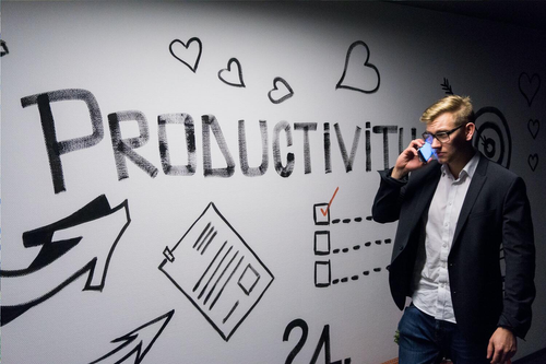 A man talks on the phone in front of a productivity sign.