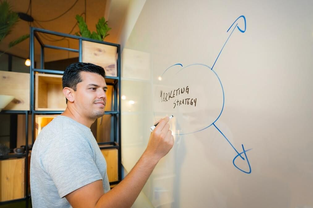 Man writing a marketing strategy on a board