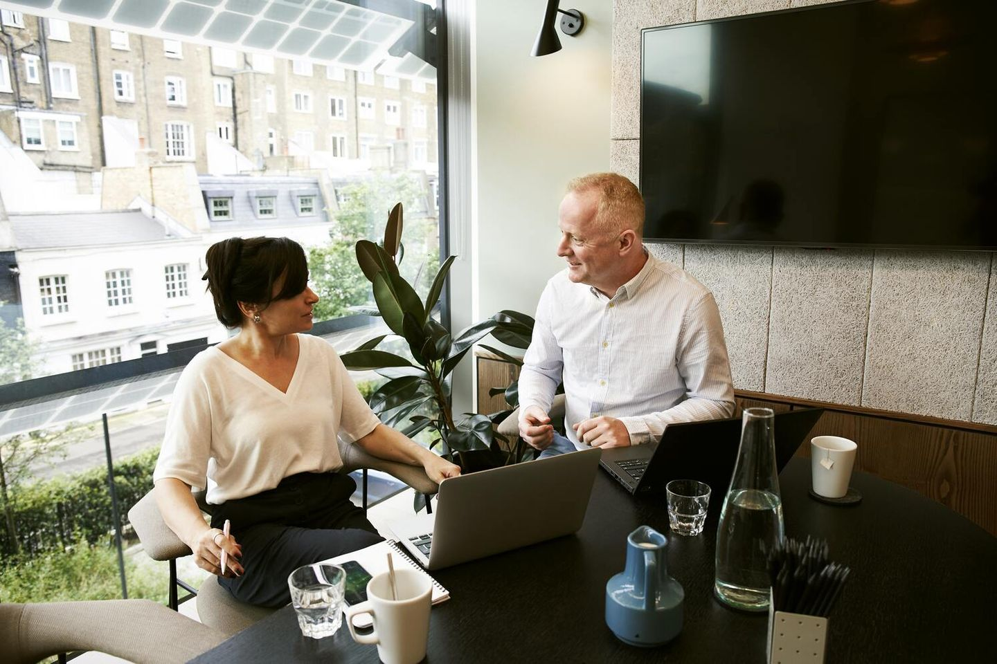 A freelance consultant and a client sit in an office at a desk discussing digital marketing