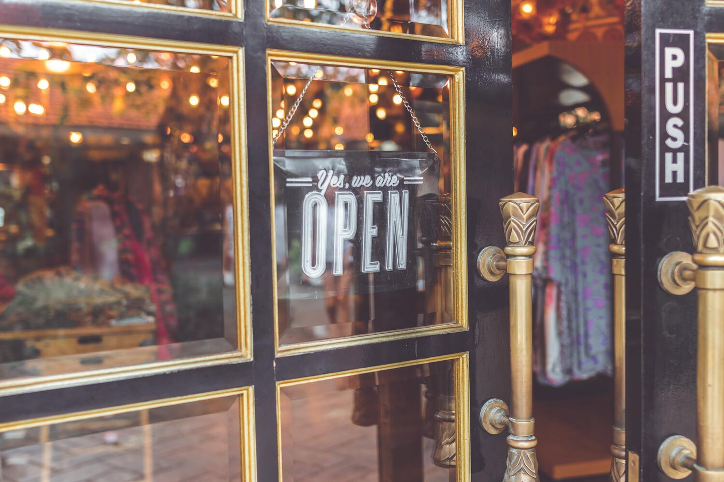 """Close-up photo of a business's door with an """"open"""" sign"""