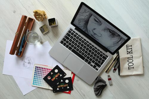 A graphic designer's workspace featuring sketches, pens, and color swatches.
