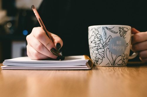 Freelance writer sitting at a desk, writing in a notebook while drinking from a mug