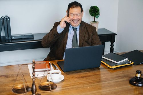 Male consultant sitting at a table, smiling while talking on the phone, working on a laptop