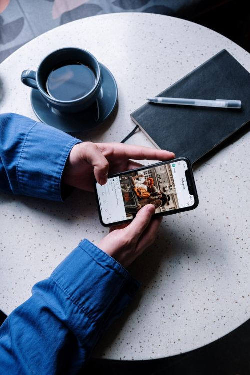 A social media manager scrolls through Instagram on their phone.