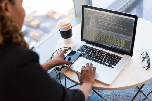 Freelance web design developer looking at code on a Macbook beside a large window