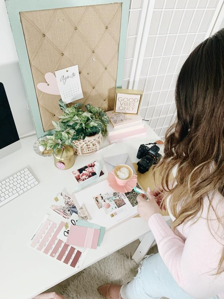 Woman standing in front of a table choosing color schemes to define and develop her personal brand