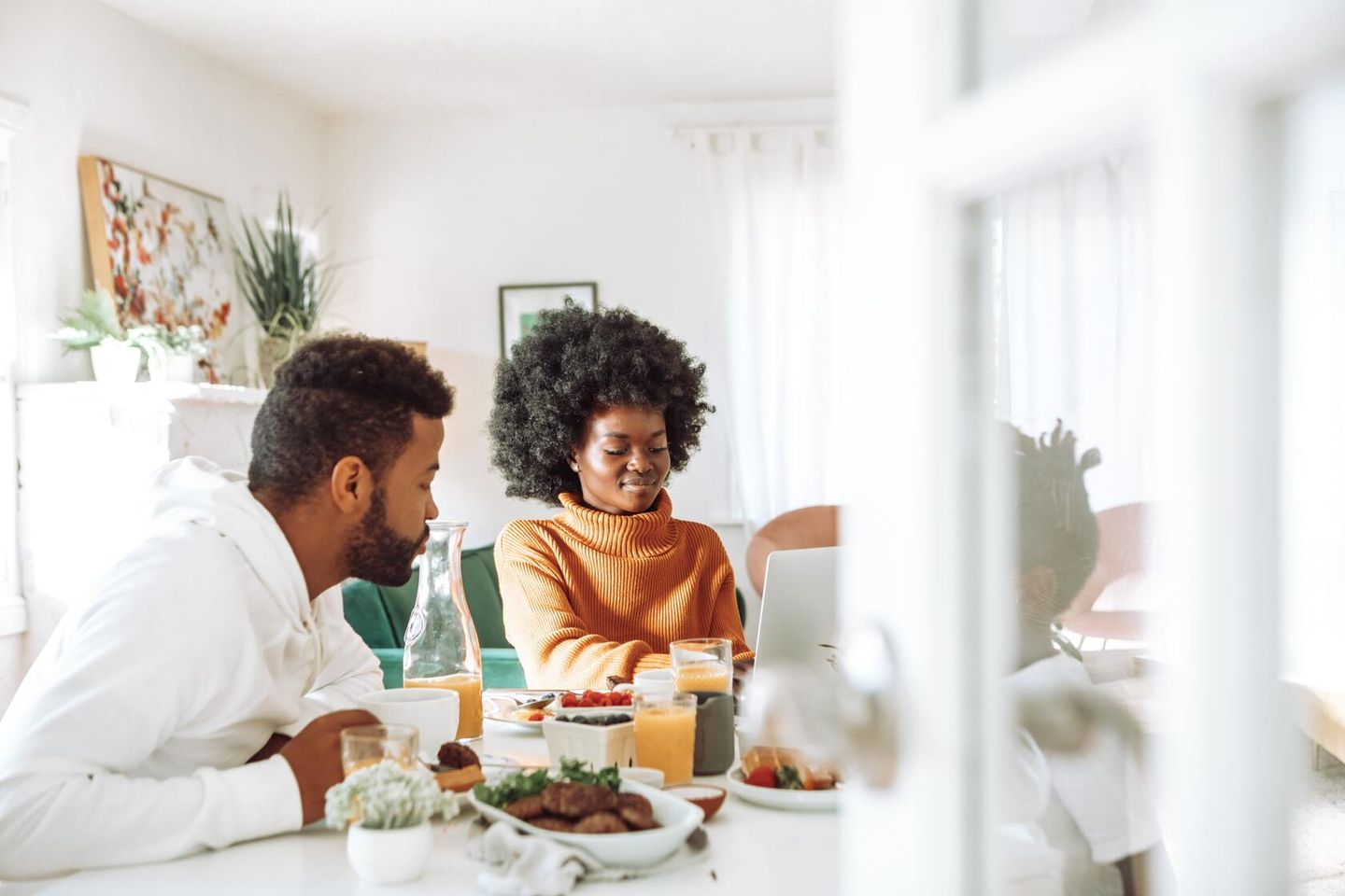 Family sits at the breakfast table while mom works from home on her laptop and talks to dad