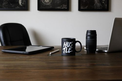 """Digital marketing tools including tablet, computer and camera on table with a coffee mug that reads """"HUSTLE"""" on it."""