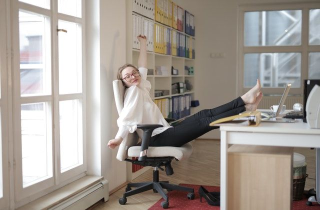 Virtual assistant sitting in desk chair, leaned back with her feet on the desk