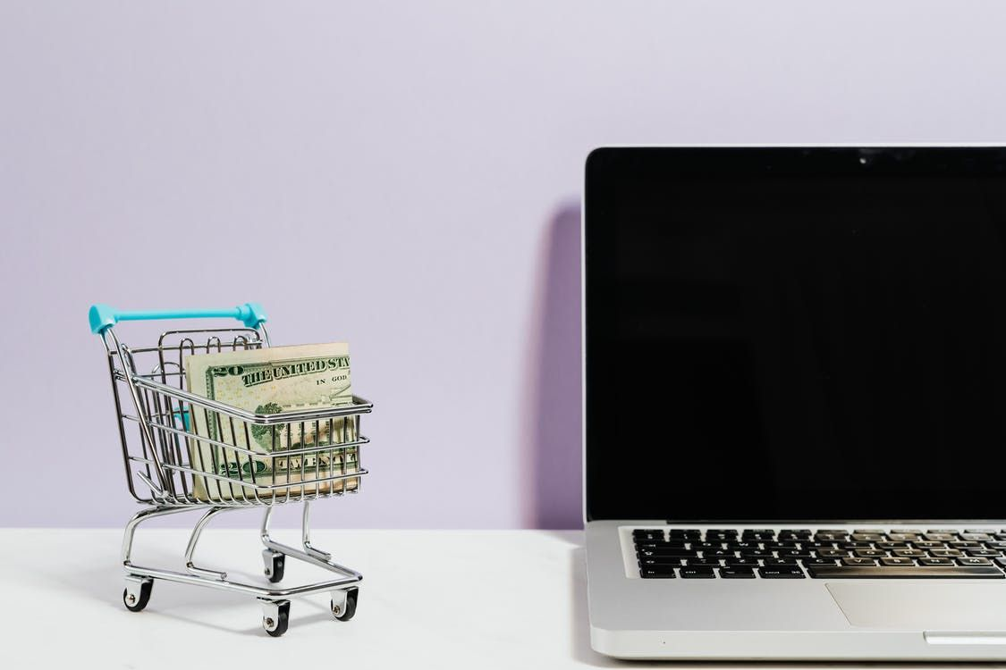 A shopping cart full of money sits next to a laptop