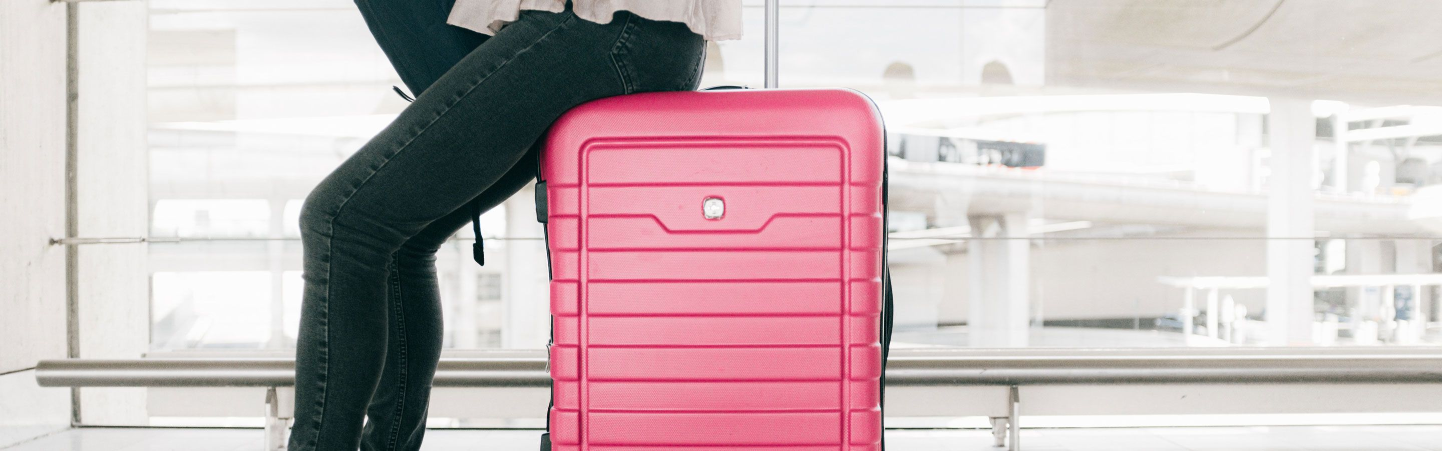 Freelancer sitting on suitcase ready for going back to work after the holidays