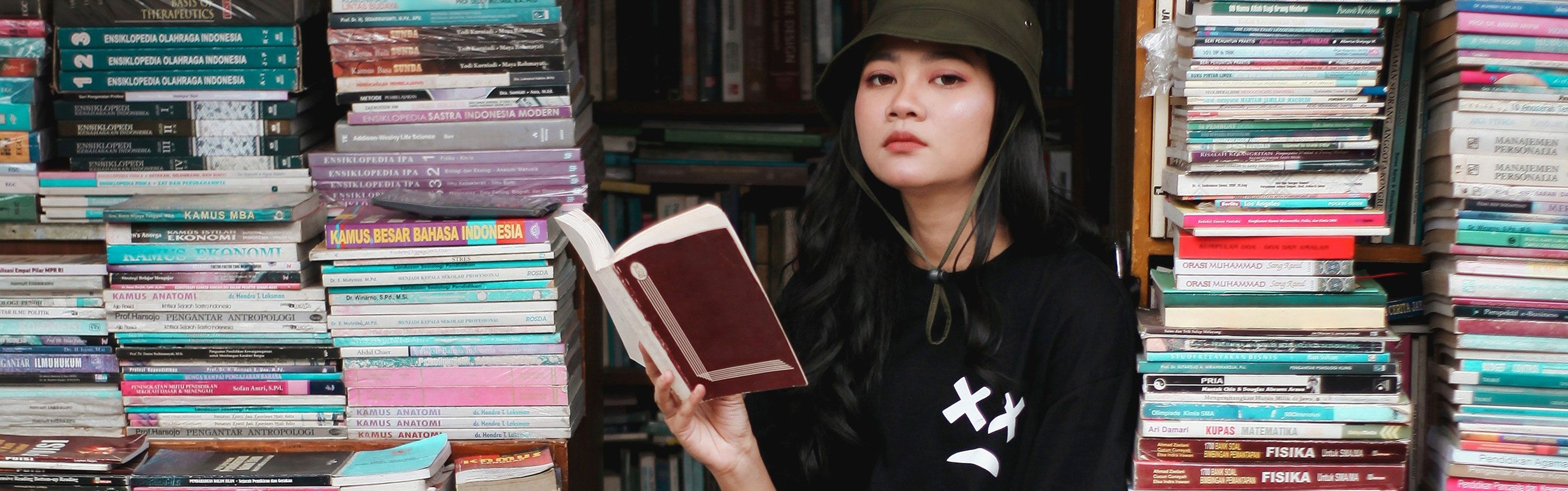 Freelancing sitting on books that she read and help her with her freelance business