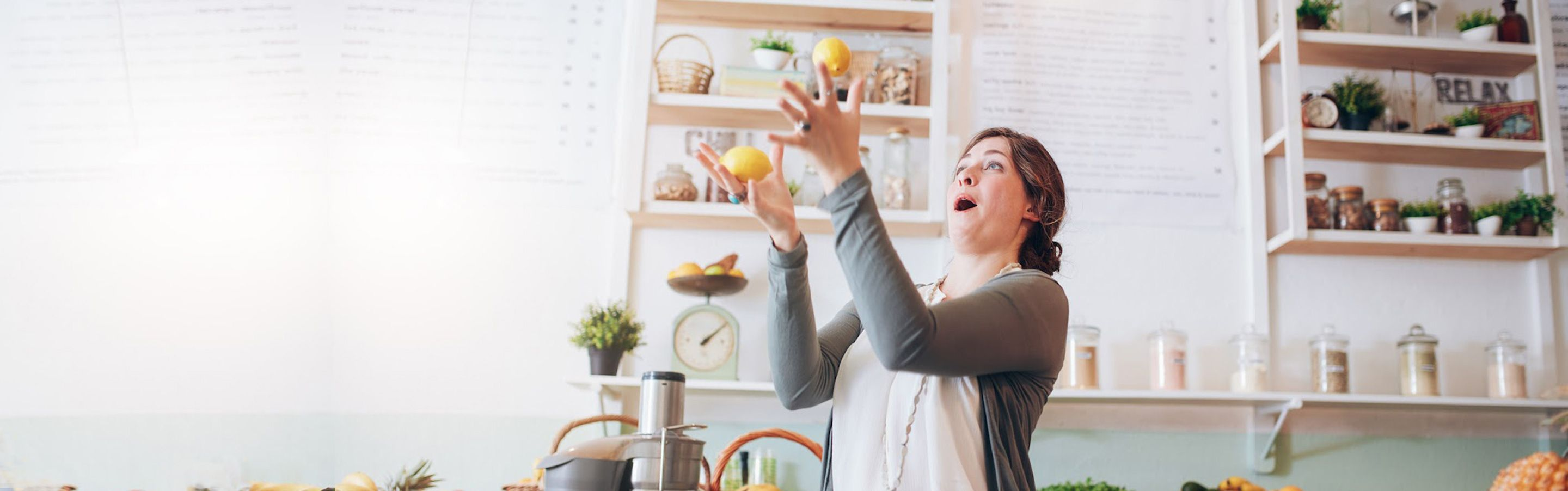 Woman juggling lemons in the kitchen.