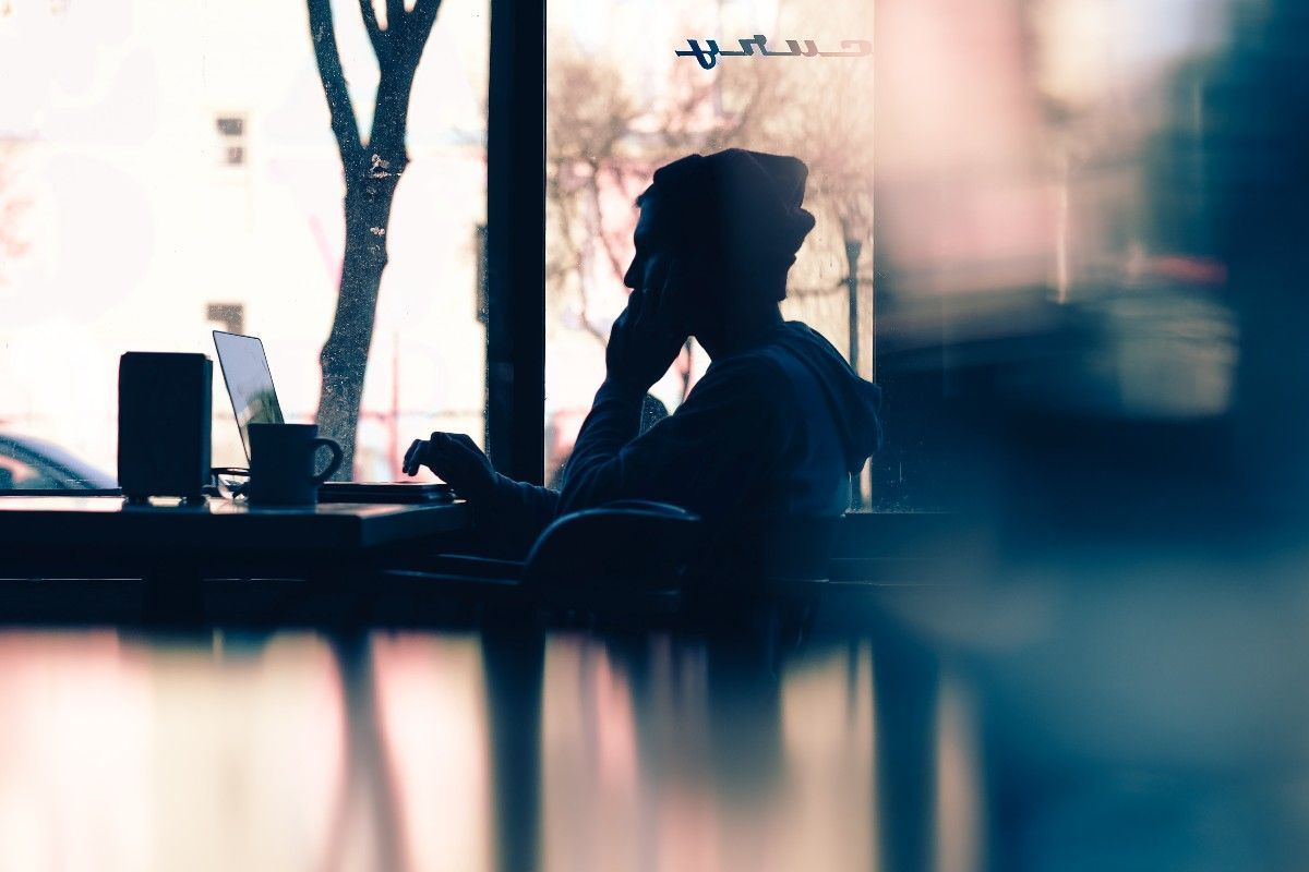 A freelancer on their laptop in a cafe looks out the window