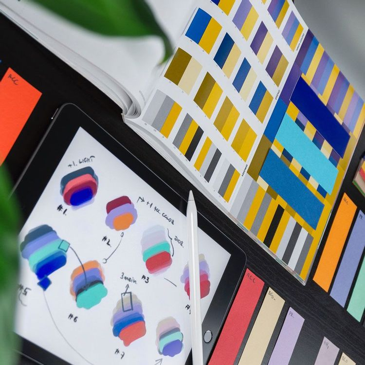 A graphic designer's workspace featuring sketches and color swatches.