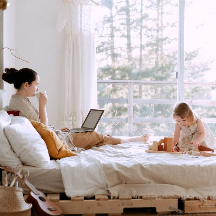 Mom sitting on bed with coffee and laptop with toddler playing on bed