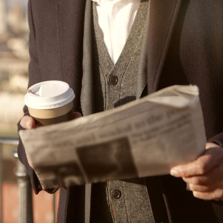 Journalist holding coffee and newsletter