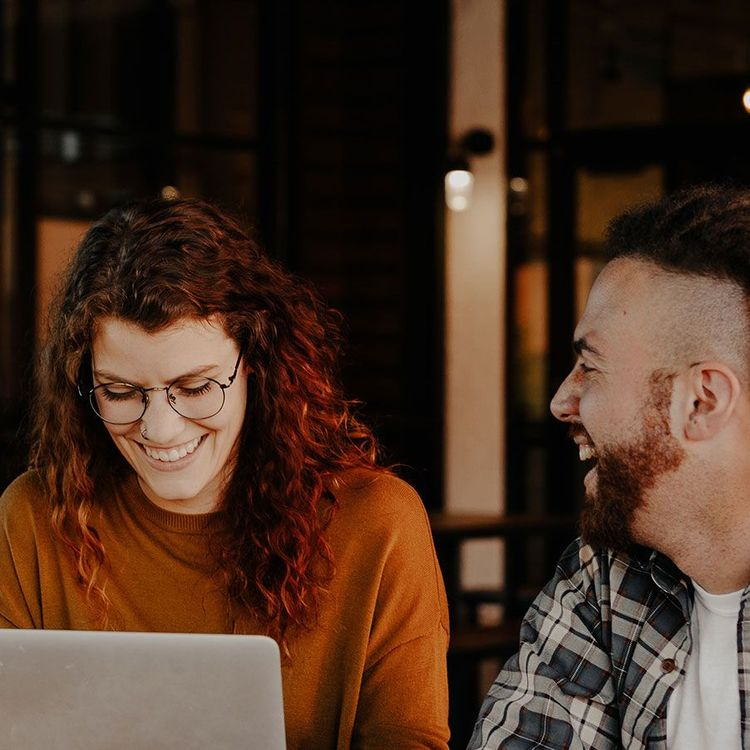 Two people laughing at a computer