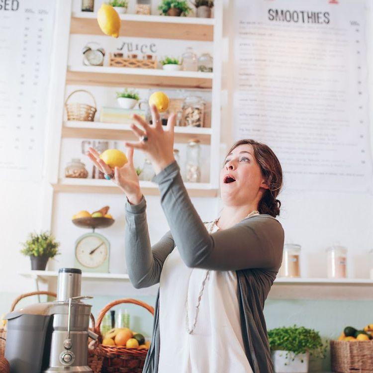 Woman juggling lemons in the kitchen.