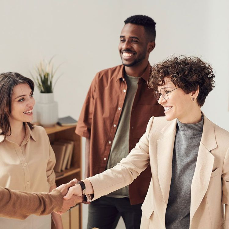 Multicultural group of four people networking and shaking hands