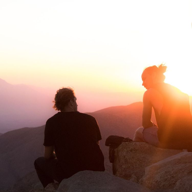 Two men sit on a rock at sunset in the mountains