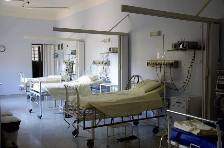 A hospital room full of empty beds and equipment.