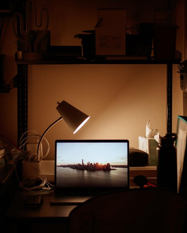 Lamp lighting a desk in a dark room.