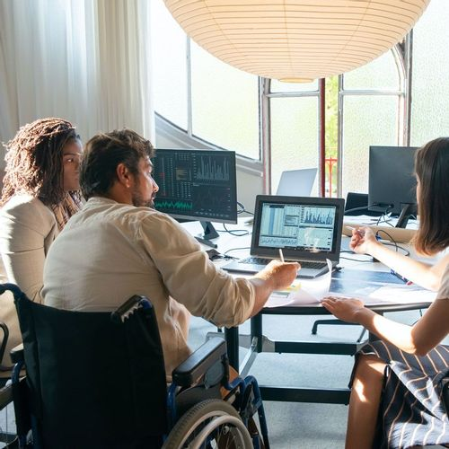 Man in a wheelchair at a computer working with two female coworkers