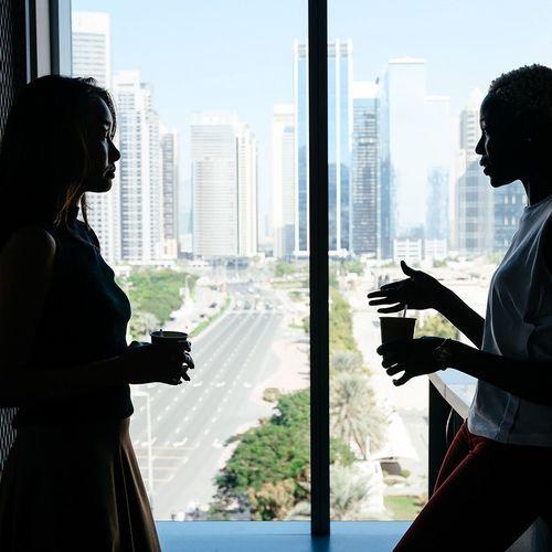 Two women backlit in a room talking by a window