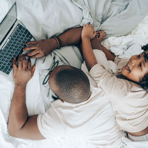 Man laying on bed working on laptop while his daughter players with him