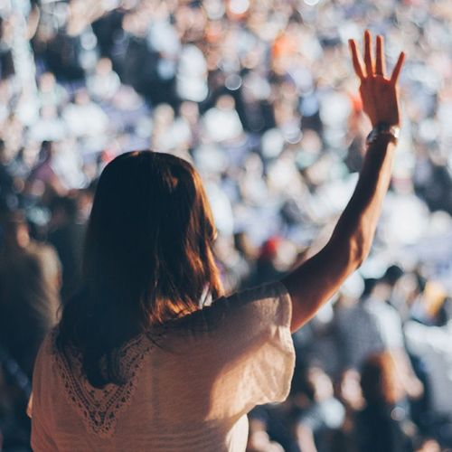 Female Freelancer in large crowd with hand up
