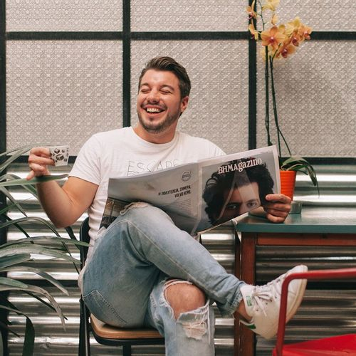 Man holding small mug and reading a newspaper while smiling.