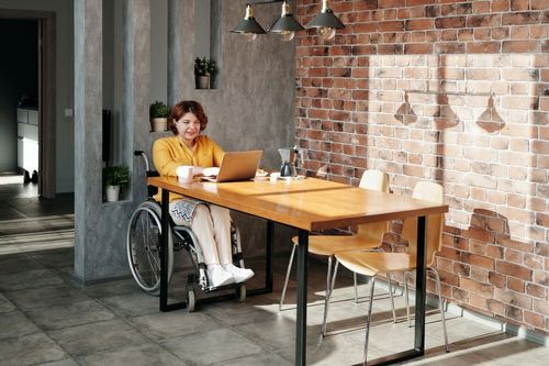 A woman in a wheelchair sips coffee in front of her laptop in an office