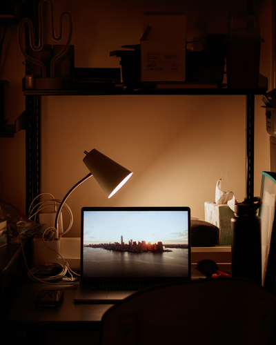 Lamp lighting a desk in a dark room.